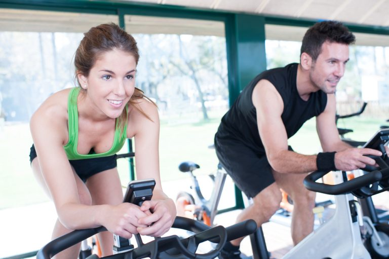 spin bike flywheel weight heavy vs light - couple working out