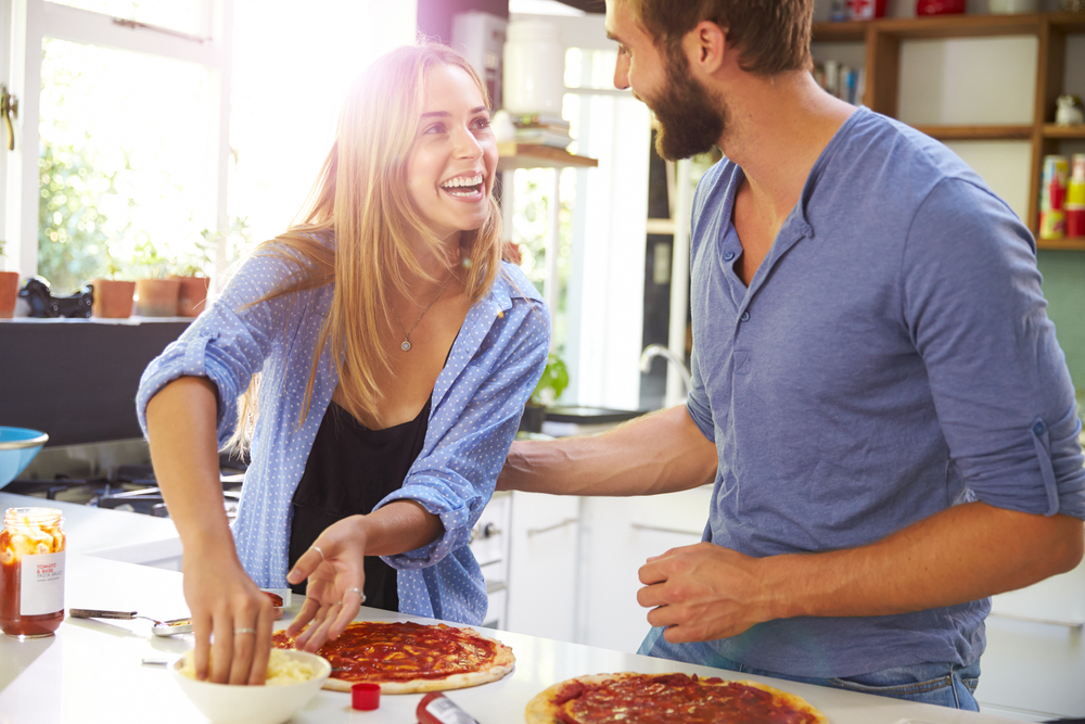 young couple enjoying cooking at home