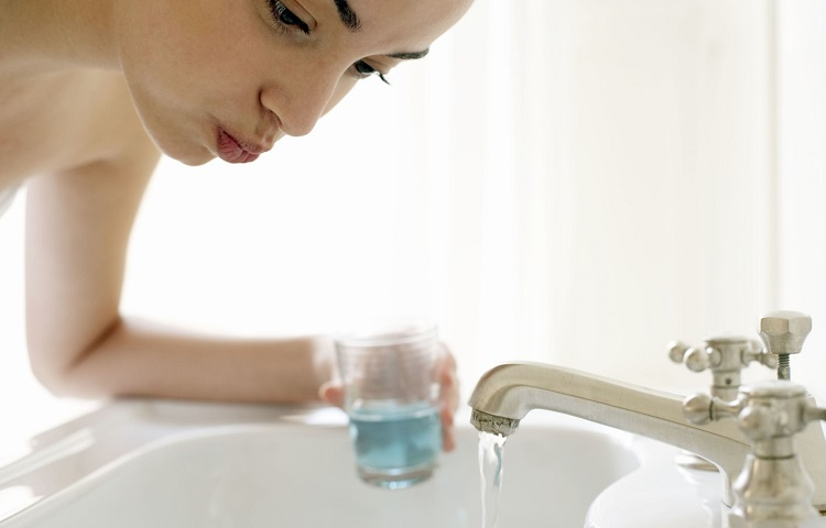 young-woman-rinsing-mouth-leaning-over-sink